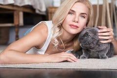Femme blonde se trouvant sur le plancher avec le chat Images stock