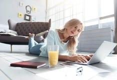 Femme blonde se trouvant sur le plancher et à l'aide de l'ordinateur portable Images stock