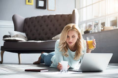 Femme blonde se trouvant sur le plancher et jugeant le jus en verre Photographie stock libre de droits