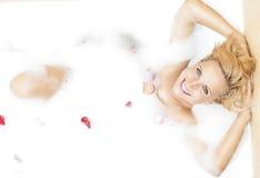 Femme blonde sensuelle caucasienne se reposant dans la baignoire mousseuse Photo stock