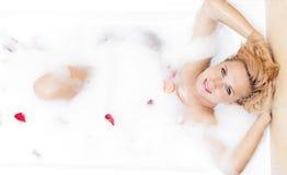 Femme blonde sensuelle caucasienne se reposant dans la baignoire mousseuse Image libre de droits