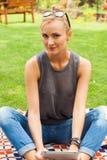 Femme blonde sensuelle s'asseyant en parc sur la couverture Elle emploie merci Photos libres de droits
