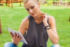 Femme blonde sensuelle s'asseyant en parc sur la couverture Elle emploie merci Photographie stock