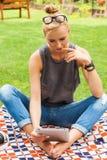 Femme blonde sensuelle s'asseyant en parc sur la couverture Elle emploie merci Photos stock