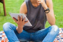 Femme blonde sensuelle s'asseyant en parc sur la couverture Elle emploie merci Image libre de droits