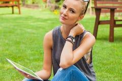 Femme blonde sensuelle s'asseyant en parc sur la couverture Elle emploie merci Images libres de droits