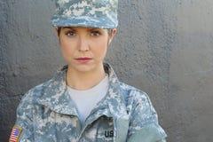 Femme blonde sexy avec le drapeau des Etats-Unis sur l'uniforme d'armée posant au mur gris Images libres de droits