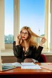 Femme blonde sexy d'affaires parlant au téléphone dans le bureau Images libres de droits