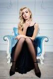 Femme blonde sexy dans la robe bleu-foncé sur la chaise Image libre de droits