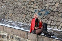 Femme blonde sexy dans la veste en cuir rouge avec une rose image libre de droits