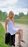 Femme blonde sexy s'asseyant par la route Photographie stock libre de droits