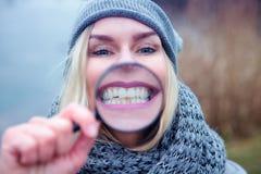 Femme blonde souriant par une loupe photographie stock