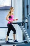 Femme blonde sportive s'exerçant sur le tapis roulant Image stock