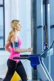 Femme blonde sportive s'exerçant sur le tapis roulant Photo stock