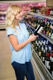 Femme blonde tenant la bouteille de vin Image stock