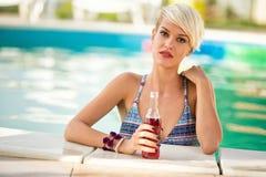 Femme blonde tenant le bord proche de piscine avec la boisson régénératrice Photos stock