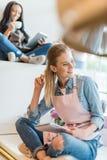 Femme blonde tenant le carnet et semblant partie tandis que café potable de collègue et à l'aide du comprimé numérique derrière photographie stock