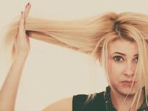 Femme blonde tenant ses cheveux secs photo libre de droits