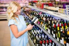 Femme blonde tenant une bouteille de vin Photographie stock