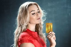 Femme blonde tenant une carte d'or Image libre de droits