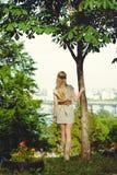 Femme blonde tendre étreignant un tronc d'arbre et examinant la distance, habillée dans une robe naturelle, élégant et confortabl Photographie stock libre de droits