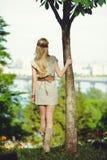 Femme blonde tendre étreignant un tronc d'arbre et examinant la distance, habillée dans une robe naturelle, élégant et confortabl images libres de droits