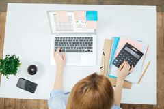 Femme blonde travaillant sur l'ordinateur portable à sa table Photo stock
