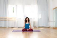 Femme bouclée de brune s'asseyant en position de lotus sur le tapis à l'intérieur photo libre de droits