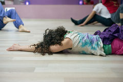 Femme bouclée de brune se trouvant sur le plancher dans le hall photographie stock libre de droits