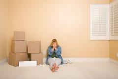 Femme bouleversé sur l'étage à côté des cadres et du signe blanc photo stock