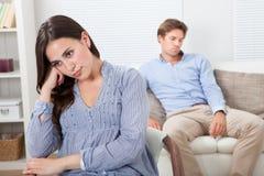 Femme bouleversée avec l'homme s'asseyant sur le sofa à l'arrière-plan Photo stock