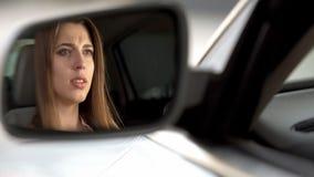 Femme bouleversée de jeunes s'asseyant dans la voiture et la route de observation, la concentration et l'attention image libre de droits