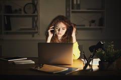 Femme bouleversée parlant au téléphone tout en travaillant sur l'ordinateur portable Photos stock