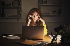 Femme bouleversée parlant au téléphone tout en travaillant sur l'ordinateur portable Image libre de droits