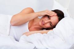 Femme bouleversée se trouvant sur le lit photo libre de droits