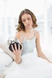 Femme bouleversée tenant un réveil le regardant se reposant sur son lit Photos stock