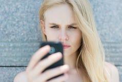 Femme bouleversée tenant un téléphone portable photos stock