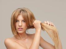 Femme bouleversée tirant les pointes fourchues de cheveu sec Image libre de droits