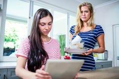 Femme bouleversée montrant les plats sales à l'ami Photographie stock libre de droits
