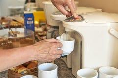 Femme brassant un thé de pot thermo dans la cuisine d'hôtel photographie stock