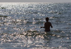 Femme bronzée de torse nu allant nager en mer brillante Image stock