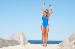 Femme bronzée sexy dans le maillot de bain en un seul morceau bleu sur la plage tropicale Image libre de droits