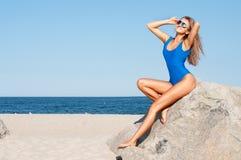 Femme bronzée sexy dans le maillot de bain en un seul morceau bleu sur la plage tropicale Photographie stock libre de droits