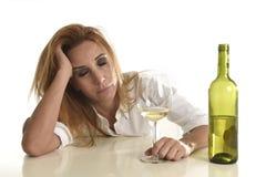 Femme bue par alcoolique gaspillé et déprimé blond buvant triste désespéré en verre de vin blanc Photos stock