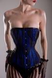 Femme burlesque d'une forte poitrine dans le corset noir et bleu Image stock