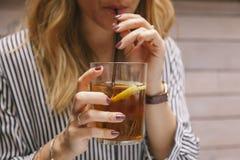 Femme buvant du thé glacé avec une paille Image libre de droits