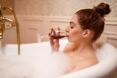 Femme buvant du vin rouge dans la baignoire Photo libre de droits