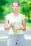 Femme buvant l'eau minérale froide d'une bouteille après la forme physique ex Photos stock