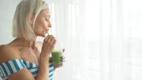 Femme buvant le smoothie végétal vert à la cuisine Mode de vie sain de consommation banque de vidéos