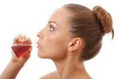 Femme buvant un liquide rouge photographie stock libre de droits